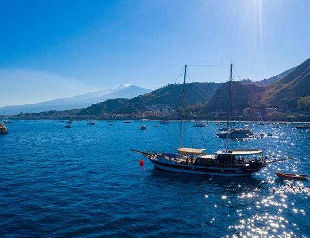 Boat in the Mediterranean sea with Etna